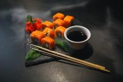 Sushibroodje met roomkaas en gebraden zalm Is verbeterd met eetstokjes van sojasaus, met meer broodjes op zwarte royalty-vrije stock foto