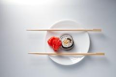 Sushibroodje op kleine plaat met eetstokjes royalty-vrije stock afbeelding