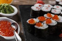 Sushibroodjes en ingrediënten op een houten oppervlakte worden gediend die royalty-vrije stock foto