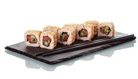 Sushibroodjes met zaden van sesam en eetstokjes, op speciale die tribune worden, op wit wordt geïsoleerd bestrooid dat Royalty-vrije Stock Foto's