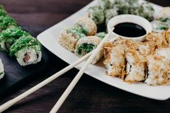 Sushibroodjes met zalm, tonijn en avocado stock afbeeldingen