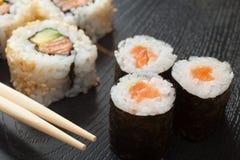 Sushibroodjes op zwarte plaat en eetstokjes Stock Foto's