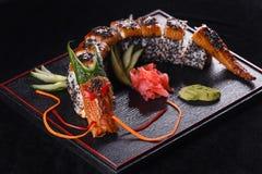 Sushidrache mit Aal, Gurke und Avocado auf einem schwarzen Hintergrund Japanisches Lebensmittel, geschmackvoll von der Mahlzeit f stockfotos