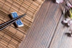 Sushiessstäbchen auf Bambustabelle mit sukura lizenzfreie stockfotografie