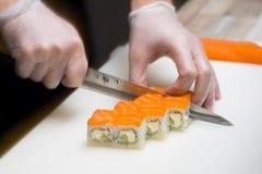 Sushiförlage, bitande sushirullar framställning av rullsushi Arkivbild