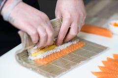 Sushiförlage, bitande sushirullar framställning av rullsushi Royaltyfri Bild