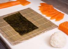 Sushiförlage, bitande sushirullar framställning av rullsushi Royaltyfri Fotografi