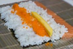 Sushiförlage, bitande sushirullar framställning av rullsushi Arkivbilder