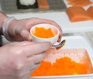 Sushiförlage, bitande sushirullar framställning av rullsushi Royaltyfria Bilder
