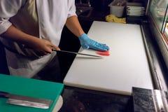 Sushikock som skivar en rå ny fisk med en skarp kniv på en whit arkivbilder