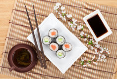 Sushimaki met zalm en komkommer en groene thee wordt geplaatst die Royalty-vrije Stock Afbeeldingen