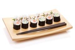 Sushimakiuppsättningen med laxen och gurkan och sakura förgrena sig Arkivfoto