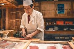 Sushimeisterkoch, der frisches Thunfischsashimifrühstück am Tsukiji-Fischmarkt in Tokyo zubereitet stockfotos