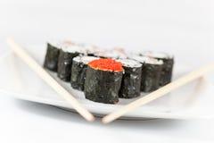 Sushimenü und -essstäbchen auf Platte, weißer Hintergrund Lizenzfreie Stockbilder