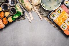 Sushimenyn med sommarrullar i rispapperomslag och misosoppa på grå färger på grå färger stenar bakgrund, den bästa sikten, gräns Royaltyfri Bild