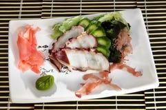 Sushimenyn skivade bläckfisken, gurkan och havsväxt Royaltyfri Fotografi