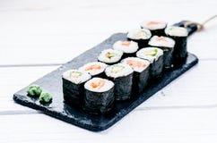 Sushireeks op een zwarte lei wordt gediend die Sushibroodjes en sashimi op een houten witte lijst Zeevruchten Ruwe Vissen Witte a Royalty-vrije Stock Foto's