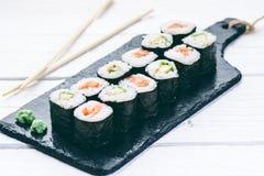 Sushireeks op een zwarte lei wordt gediend die Sushibroodjes en sashimi op een houten witte lijst Zeevruchten Ruwe Vissen Witte a Royalty-vrije Stock Fotografie