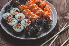 Sushirolle mit Lachsen, Gurke, Avocado, roter Kaviar mit Essstäbchen Sushimenü Japanische Nahrung Schließen Sie oben, auf Bambus stockbilder