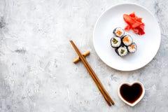 Sushirolle mit Lachsen und Avocado auf Platte mit Sojasoße, Essstäbchen, Wasabi auf Draufsicht des grauen Steinhintergrundes Stockfotografie