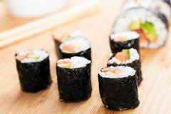 Sushirollen mit Lachsen, Avocado, Reis in der Meerespflanze und Essstäbchen Lizenzfreie Stockfotos