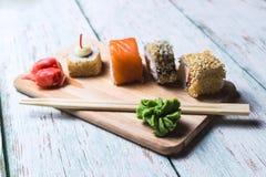 Sushirollen mit Sojasoße, Wasabi und in Essig eingelegtem Ingwer Stockbild