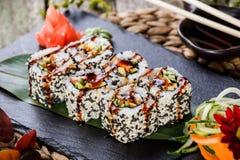 Sushirollen stellten mit Garnelentempura, -gurke, -avocado und -indischem Sesam auf schwarzem Stein auf Bambusmatte, selektiver F Stockbild