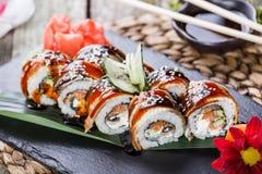 Sushirollen stellten mit Lachs-, Frischkäse, Gurke, indischem Sesam und Wasabi auf schwarzem Stein auf Bambusmatte, selektiver Fo Stockbilder