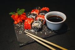 Sushirulle med gräddost och den stekte laxen Väljas upp med pinnar från soya, med mer rullar på svart arkivfoto