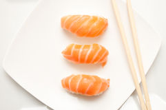 Sushis and  chopsticks on white plate Royalty Free Stock Photo