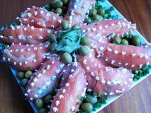Sushisalatkraken-Meeresfrüchteteller eingewickelt in einer Platte von roten Fischen Lizenzfreie Stockfotos