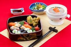 Sushiuppsättning: sashimi- och sushirullar på röd bakgrund Royaltyfri Fotografi