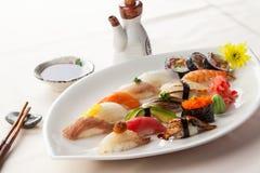 Sushiuppsättning: sashimi- och sushirullar på vit bakgrund Arkivbilder