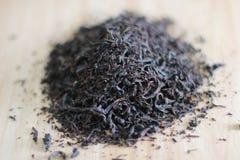 Susi czarni herbaciani liście na drewnianym stole fotografia royalty free