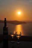 Susnet de caldeira de Santorini avec la bouteille de vin Image stock