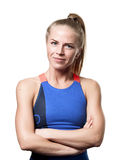 Suspecting Blue eyed blond girl. Blue eyed blond girl with tail hair in sportswear with crossed arms and front standing on white isolated background Royalty Free Stock Photography