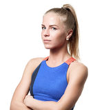 Suspecting Blue eyed blond girl. With tail hair in sportswear with crossed arms and side standing on white isolated background Stock Image