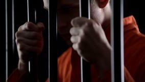 Suspeito em barras da prisão da terra arrendada da cadeia, esperando a experimentação, esperando evitar a punição foto de stock royalty free
