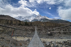 Suspencion bridge across the mountain river in Himalayas Stock Photos