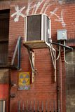 Suspended Air Conditioning unit in a city alley Royalty Free Stock Images