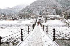 The suspended bridge entrance of Shirakawago in winter, Japan. The entrance of Shirakwago village Japan with tourists crossing suspended bridge over a river in stock photography