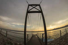 Suspended bridge ship dock and sunset Royalty Free Stock Images