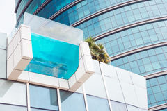 Suspended Pool. A swimming pool with a clear bottom, suspended on a hotel`s facade Stock Images