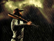 Suspended by the rain. Baseball player looking at the dark sky, while the rain is falling Royalty Free Stock Images