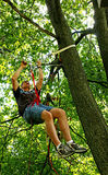 Suspended from ropes in a Tree. A man is suspended in a tree top high off the ground by ropes, pulleys and a harness stock photography