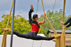 Suspended Splits. An aerialist with her feet wrapped in silk, hangs suspended in the splits during an outdoor performance Stock Photo