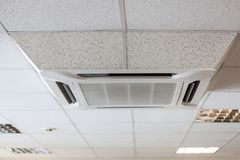 Suspended tile ceiling with big air-conditioner unit, office room Stock Photography