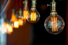 Suspended under the ceiling light bulbs in retro style. Close-up in the darkness Stock Photos