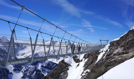 Suspended walkway over snow mountains Royalty Free Stock Photography