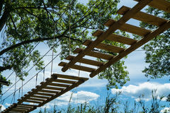 Suspended wood ladder in an outdoor rope park royalty free stock photography